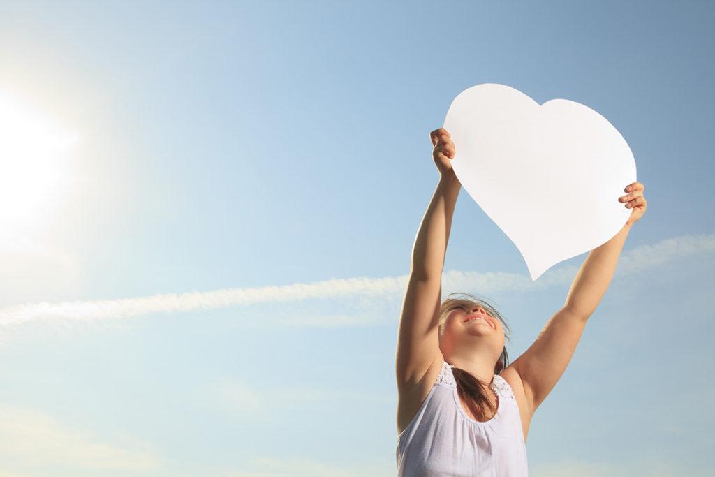 Barn, der holder et hjerte op mod himlen