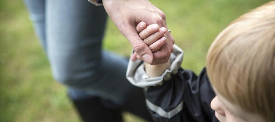 Barn ogg voksen holder hånd. Foto: Mark Knudsen